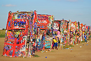Kids clinbing on Cadillac Ranch. Caddilac Ranch is a public art installation and sculpture in Amarillo, Texas, U.S. It was created in 1974 by Chip Lord, Hudson Marquez and Doug Michels, who were a part of the art group Ant Farm.