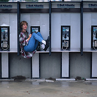 USA, Maryland, (MR) Marianne Bakia curls into phone booth to avoid rain in Bethesda