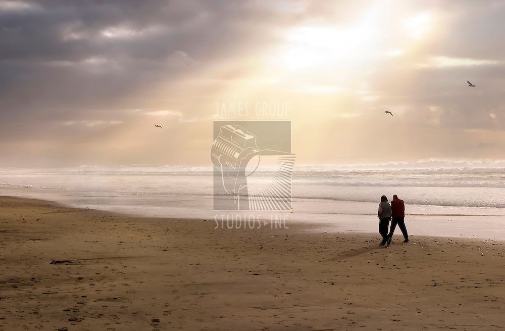 A peaceful beach scene with powerful sun-rays beaming through the clouds & showing a couple walking.