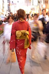 Blur motion image of woman wearing kimono walking in central Tokyo Japan