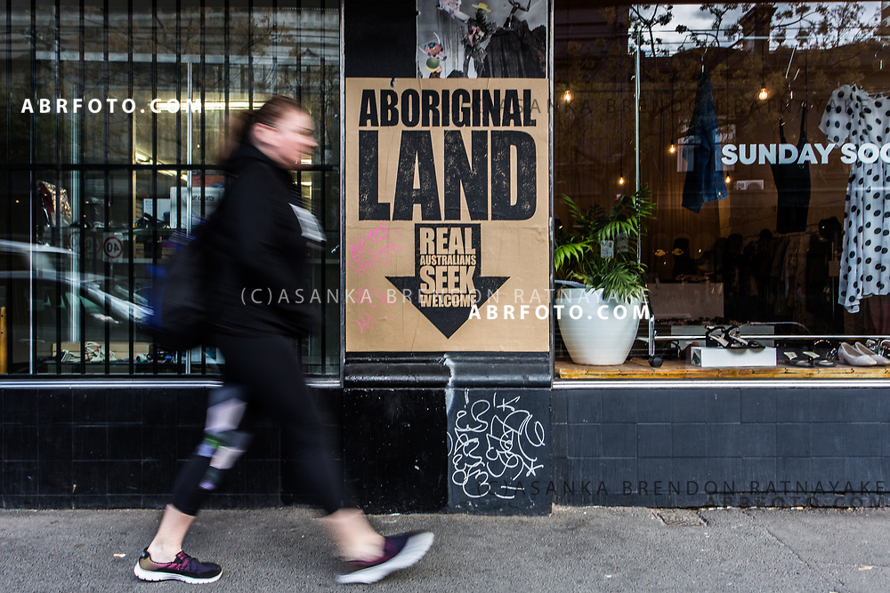 A person walks past a street poster reading 'Aboriginal land, Real Australians seek welcome' which is pasted along a row of shops on Gertrude street in Melbourne, Australia, September 1, 2017. Asanka Brendon Ratnayake for the New York Times