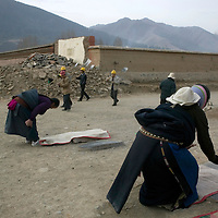 APRIL 5, 2012 : Tibetan nomads pray in the streets of Labrang monastery as Chinese workers walk past them.