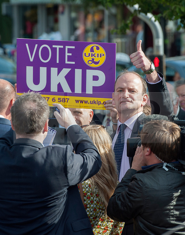 © Licensed to London News Pictures. 29/08/2014. Clacton-on-Sea, UK Douglas Carswell gives a thumbs up to a passing motorist. Douglas Carswell and Nigel Farage, Leader of the UK Independence Party, UKIP, meet local people on a walk about in Clacton-on-Sea today 29th August 2014. Tory Douglas Carswell  defected to UKIP and quit as MP for Clacton, saying he will contest the subsequent by-election for Nigel Farage's party.. Photo credit : Stephen Simpson/LNP