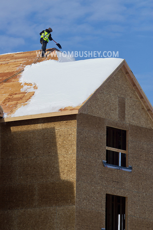 Middletown, New York - A worker clears snow from the roof of a building under construction after a snowstorm on Feb. 6, 2014.