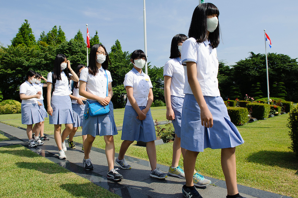High school students wear protective masks during Memorial Day observances at the United Nations Memorial Cemetery in Busan, South Korea. Opposition politicians have criticized the administration of Park Geun-hye for its initial response to the MERS outbreak. 41 people so far have been diagnosed with the disease, with four deaths.
