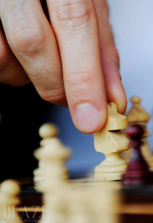 Male hand moves a knight while playing chess.