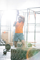 Determined man hitting tire with sledgehammer in crossfit gym