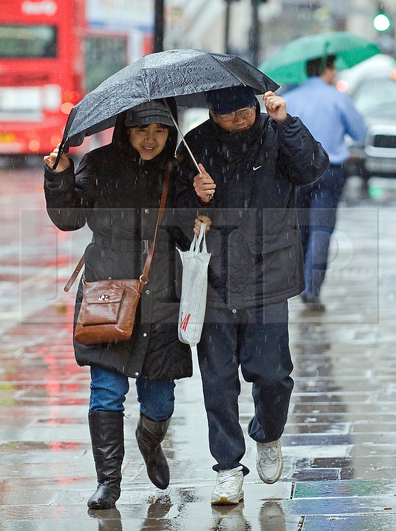 © Licensed to London News Pictures. 03/01/2012. London, UK.  Two people sharing an umbrella battle through heavy rain and winds in central London on January 3rd, 2011. Severe weather warnings issued as storms hit UK . Photo credit : LNP
