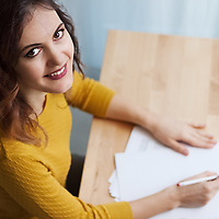 Young caucasian brunette woman taking notes and smiling at camera. Indoor setting