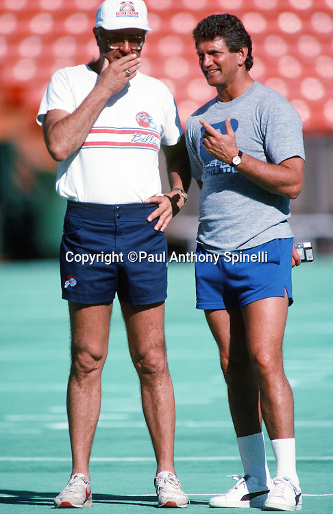 Former Washington Redskins quarterback Joe Theismann (right) talks to a coach while watching the American Football Conference practice during the week before the 1989 NFL Pro Bowl football game against the National Football Conference on Jan. 24, 1989 in Honolulu. The NFC won the game 34-3. (©Paul Anthony Spinelli)