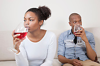 Young African American couple drinking red wine at home