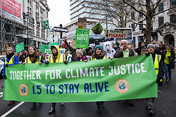 London, UK. 1st December, 2018. Environmental campaigners pass in front of the Brazilian embassy on the Together for Climate Justice demonstration in protest against Government policies in relation to climate change, including Heathrow expansion and fracking. Following a rally outside the Polish embassy, chosen to highlight the UN's Katowice Climate Change Conference which begins tomorrow, protesters marched to Downing Street.