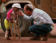 Dr. Rick Hodes, director of the International Rescue Committee field hospital at the  sprawling Kibumba refugee camp in Goma, Zaire, lets  4-year-old Uboniragira (no last name) listen to his heart with a stethoscope while the child was learning to walk with crutches after losing a foot after being hit by a car at the camp in December. Berkins (9 of 14)