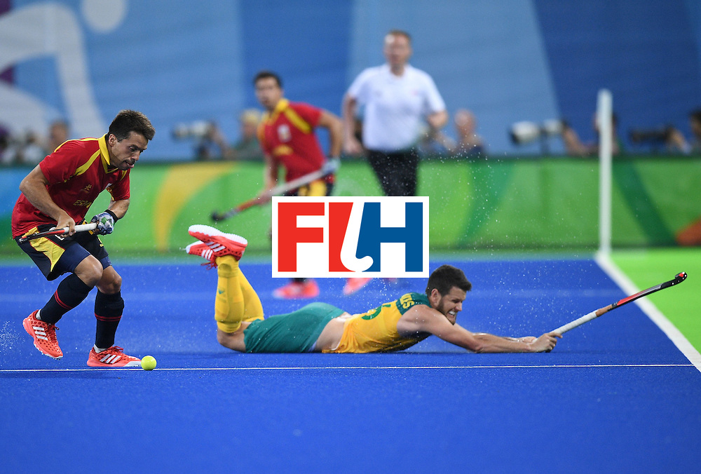 Australia's Matt Gohdes (R) falls as Spain's Marc Salles controls the ball during the men's field hockey Australia vs Spain match of the Rio 2016 Olympics Games at the Olympic Hockey Centre in Rio de Janeiro on August, 7 2016. / AFP / MANAN VATSYAYANA        (Photo credit should read MANAN VATSYAYANA/AFP/Getty Images)
