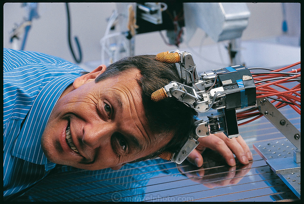 "Once intelligent robots are created, argues Kevin Warwick, (seen here clowning with a lab robot hand), of the University of Reading in the UK, it will not take them long to realize their superiority to flesh-and-blood beings. ""The human race as we know it,"" he has written, ""is very likely in its endgame"" machines will wipe us out. Believing that this dreadful scenario is unavoidable, Warwick nevertheless continues his research into robotics. From the book Robo sapiens: Evolution of a New Species, page 29."