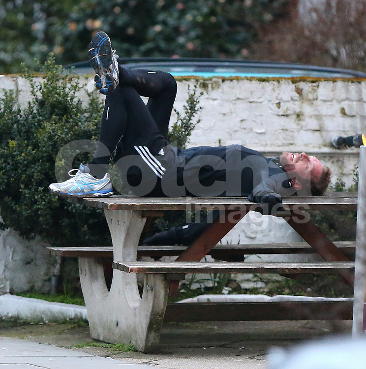 Cold Play frontman Chris Martin was spotted coming back from a long jog with friends and stopped for a breather laying flat on his back on a bench before being chauffeured home. UK. 20/03/2013<br />