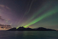 A dim but photogenic aurora on November 7, from the coast of Norway on the Hurtigruten ship the m/s Nordlys, in a view looking south to Pegasus and Andromeda, and over off-shore islands. The rising waning Moon off frame to the left illuminates the sky and landscape. <br /> <br /> This is a single 1-second exposure with the Sigma 14mm Art lens at f/1.8 and Nikon D750 at ISO 6400.