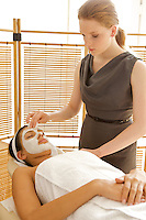 Young woman receiving facial in spa