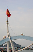 Two maintenance men working on Cat Ba harbour ferry terminal arch below the vietnam flag above fishing boats in Cat Ba Harbour, Vietnam