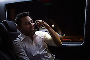 Oscar De La Hoya visits with his kids who didn't make the trip to Texas on his phone during the ride back to the hotel at the end of the night in Grapevine, Texas on September 16, 2016.  (Cooper Neill for ESPN)