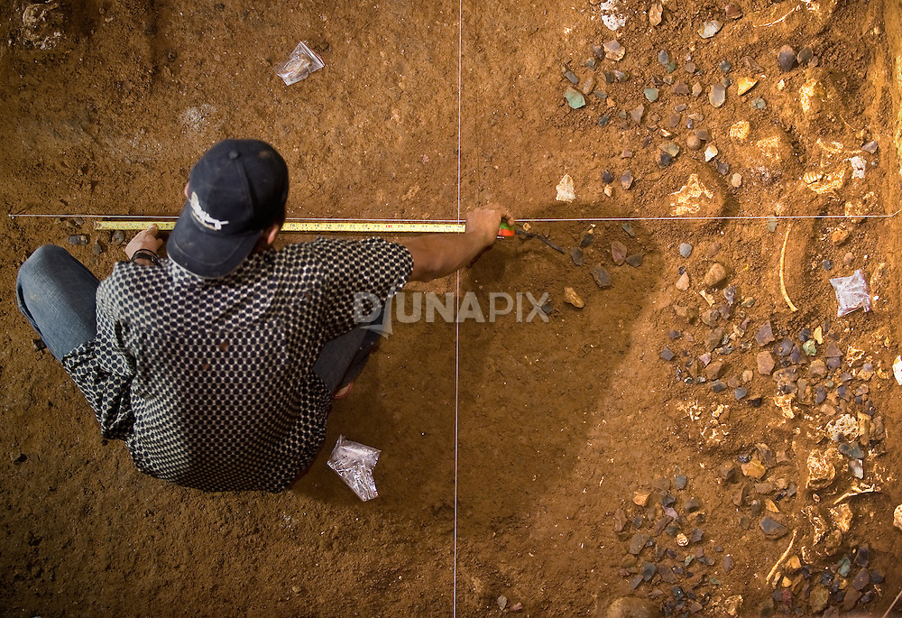 A Manggarai worker measures positions of hobbit tools densely scattered around Stegodon remains at Liang Bua cave, discovery site of the Flores hobbit, Homo floresiensis