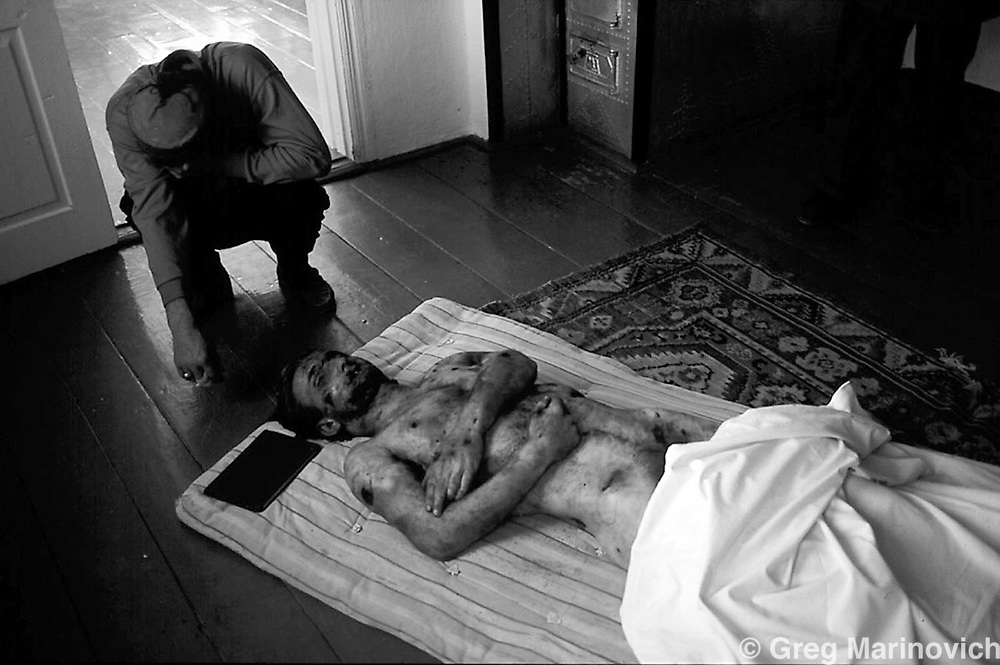 CHECHNYA JUL 1995: Family grieve over the body of a Chechen civilian tortured by Russian soldiers in Vedeno town, Aug 1995.  Russia agreed to grant them autonomy after Chechens retook several towns and the capital Grozny in 1995, after a bloody war for Chechen independence.  The Chechens are Moslem and have a strong sense of national identity.  Their fight for independence from Russia has increased an Islamic militancy and  identity. Photo by Greg Marinovich