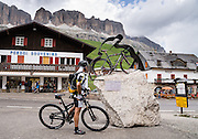 A bicycling monument at Passo Pordoi lists the King of the Mountains/KoM winners for Giro d'Italia (including Gilberto Simoni). The Sella Group rises above. Pordoi Pass (or Pordoijoch, 2239 meters/7346 feet) is the highest surfaced road traversing a pass in the Dolomites of Italy. State highway 48 is also called Grand Strader delle Dolomiti. The Dolomites are part of the Southern Limestone Alps, in Europe. UNESCO honored the Dolomites as a natural World Heritage Site in 2009.