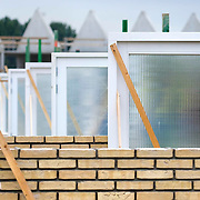 Nederland Zuid-Holland Zoetermeer  27-08-2009 20090827 Foto: David Rozing ..Serie over bouwsector.                 .Metselwerk. Fundering, karkassen schuren. Een rij muren van schuur in aanbouw. .Deuren, met op de achtergrond geraamte woningen / woningen in aanbouw. .Construction work in progress, concrete foundation, unfinished shanty.         .Holland, The Netherlands, dutch, Pays Bas, Europe ..Foto: David Rozing