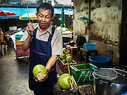 29 SEPTEMBER 2015 - BANGKOK, THAILAND:  A man cuts open coconut in Bang Chak Market. The Bang Chak Market serves the community around Sois 91-97 on Sukhumvit Road in the Bangkok suburbs. About half of the market has been torn down, vendors in the remaining part of the market said they expect to be evicted by the end of the year. The old market, and many of the small working class shophouses and apartments near the market are being being torn down. People who live in the area said condominiums are being built on the land.       PHOTO BY JACK KURTZ