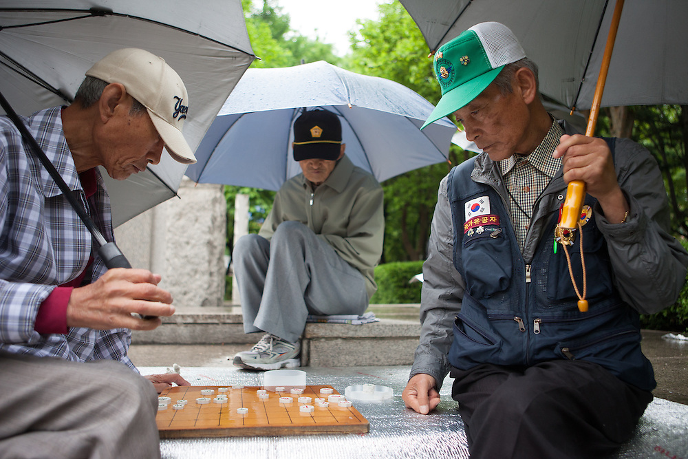 Men are playing a traditional board game in a park close to Jongmyo Shrine in the center of the Korean capital Seoul.