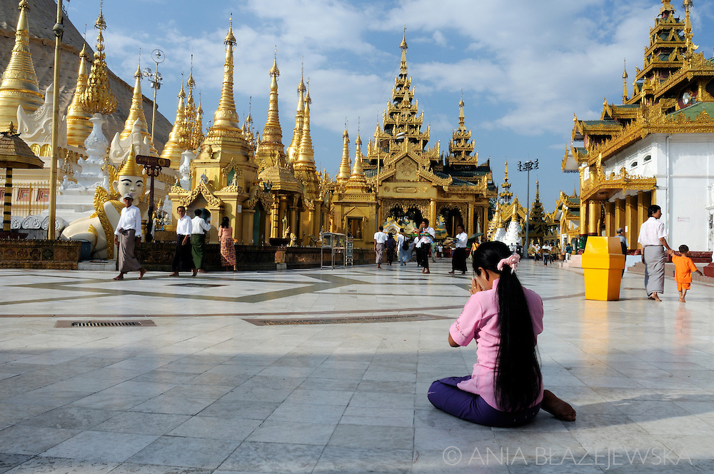 Myanmar, Yangon. Woman praying in Shwedagon Paya, the biggest and the most important buddhist temple in Yangon.