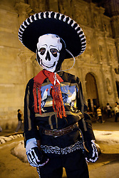 North America, Mexico, Oaxaca Province, Oaxaca, Zocalo plaza, boy dressed as skeleton in mariachi costume in front of Cathedral during Day of the Dead (Dias de los Muertos) celebration at night