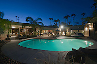 Swimming pool in front of modern mansion at night
