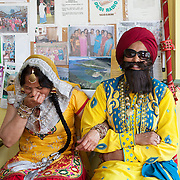Southall, Greater London, UK, August 8, 2015.<br /> Waiting for the Teeyan March to start in the Panjabi Centre/Desi Radio. Both in their 50s, Naseeb Kaur (on the right) dressed up as a man, and Chhindo Kaur (left) are active volunteers of The Panjabi Centre. On this picture, they have a good time playing a mock couple. The Teeyan Festival organized by the Panjabi Centre/Desi Radio is a time for women and girls to have fun, to feel proud and self-confident.