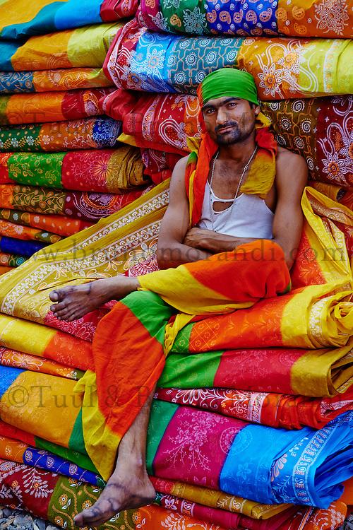 Inde, Rajasthan, Usine de Sari, Jiar Arsi, 25 ans. Les tissus sechent en plein air. Ramassage des tissus secs par des femmes et des enfants avant le repassage. Les tissus pendent sur des barres de bambou. Les rouleaux de tissus mesurent environ 800 m de long. . // India, Rajasthan, Sari Factory, Jiar Arsi, 25 old. Textile are dried in the open air. Collecting of dry textile  are folded by women and children. The textiles are hung to dry on bamboo rods. The long bands of textiles are about 800 metre in length.