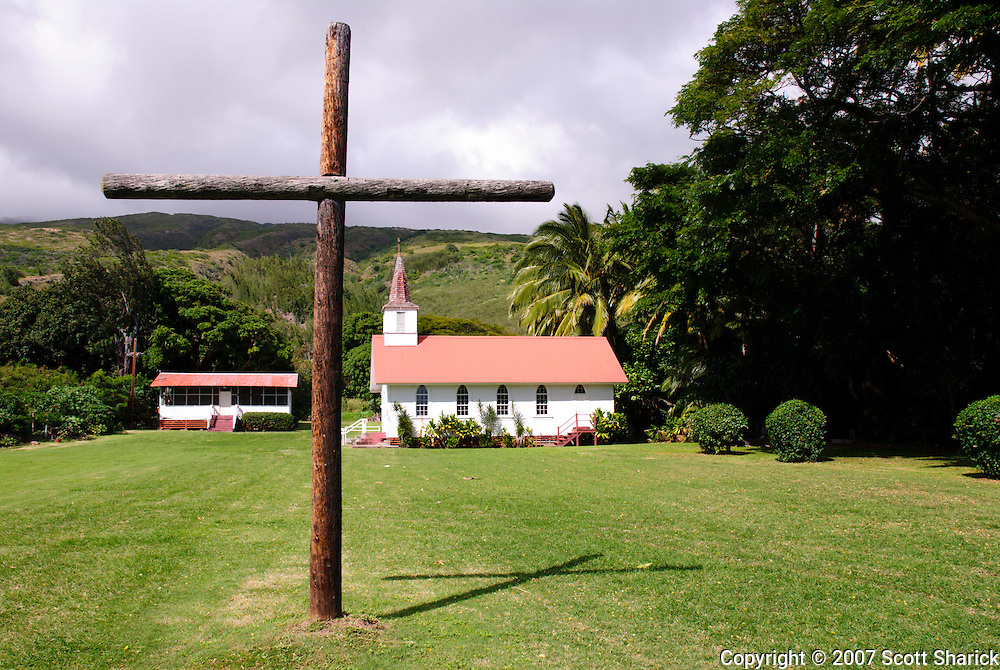A large wooden cross is placed in the front lawn of a church on the ilsand of Molokai in Hawaii.