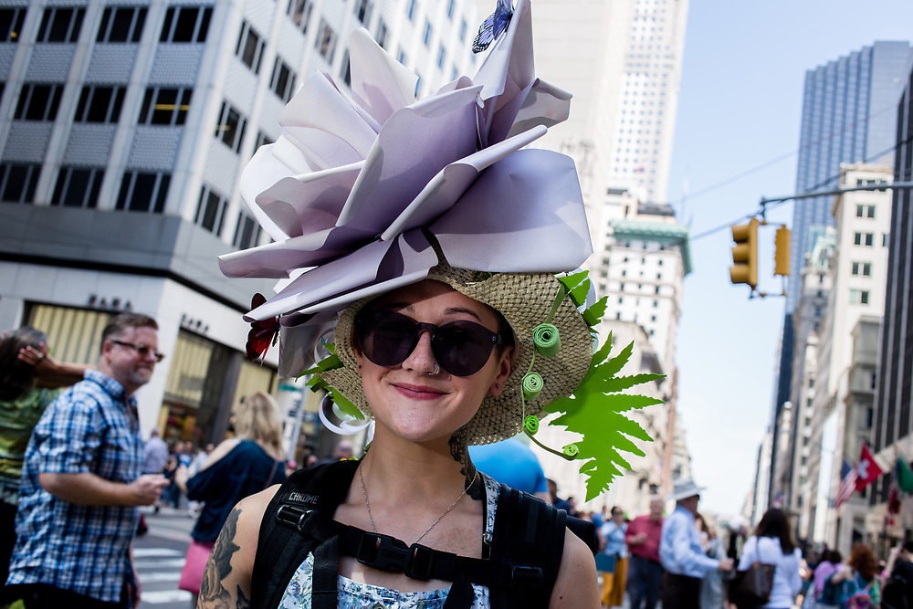 New York, NY - April 16, 2017. A young woman wears a hat topped by a giant purple bow and a butterfly New York's annual Easter Bonnet Parade and Festival on Fifth Avenue.
