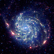 The galaxy Messier 101 is a swirling spiral of stars, gas, and dust. Messier 101 is nearly twice as wide as our Milky Way galaxy. Spitzer's view, taken in infrared light, reveals the galaxy's delicate dust lanes as yellow-green filaments. Such dense dust clouds are where new stars can form. In this image, dust warmed by the light of hot, young stars glows red. The rest of the galaxy's hundreds of billions of stars are less prominent and form a blue haze. Astronomers can use infrared light to examine the dust clouds where stars are born.