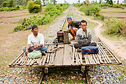 """01 JULY 2006 - PHNOM PENH, CAMBODIA: A bamboo train on the tracks in central Cambodia. The """"bamboo trains"""" run along the government tracks in rural Cambodia. Bamboo mats are fitted over wheels which ride on the rails. The contraption is powered by a either a motorcycle or lawn mower engine. The Cambodian government would like to get rid of the bamboo trains, but with only passenger train in the country, that runs only one day a week, the bamboo trains meet a need the government trains do not. While much of Cambodia's infrastructure has been rebuilt since the wars which tore the country apart in the late 1980s, the train system is still in disrepair. There is now only one passenger train in the country. It runs from Phnom Penh to the provincial capitol Battambang and it runs only one day a week. It takes 12 hours to complete the 190 mile journey.  Photo by Jack Kurtz / ZUMA Press"""