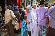 "08 AUGUST 2013 - BANGKOK, THAILAND:       People walk through the street in front of Haroon Mosque after Eid al-Fitr in Bangkok. Eid al-Fitr is the ""festival of breaking of the fast,"" it's also called the Lesser Eid. It's an important religious holiday celebrated by Muslims worldwide that marks the end of Ramadan, the Islamic holy month of fasting. The religious Eid is a single day and Muslims are not permitted to fast that day. The holiday celebrates the conclusion of the 29 or 30 days of dawn-to-sunset fasting during the entire month of Ramadan. This is a day when Muslims around the world show a common goal of unity. The date for the start of any lunar Hijri month varies based on the observation of new moon by local religious authorities, so the exact day of celebration varies by locality.   PHOTO BY JACK KURTZ"