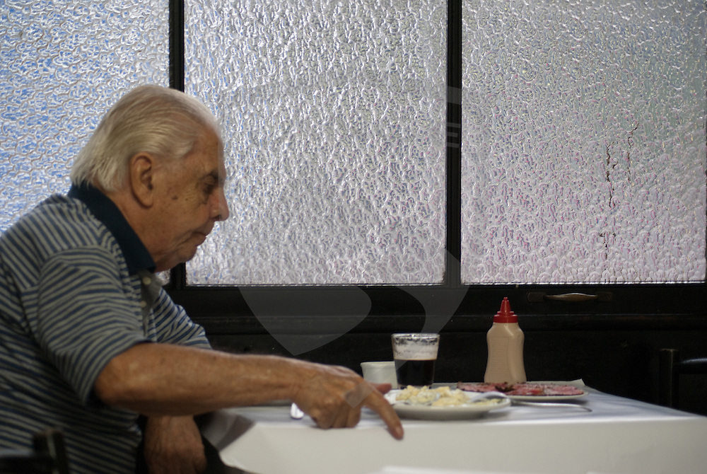 a man sitting at a table in a cafe in rio de janeiro, brazil.