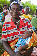 Scovia with baby Deus (2 weeks old). Women from Kitahurira, the only Batwa tribe settlement in Mpungu district, wait with their children to attend the Bwindi Community Hospital outreach clinic. The mothers and children receive nutrition information and vaccinations from the hospital nurse.  Bwindi Community Hospital provides different outreach clinics everyday for the surrounding area around Buhoma. The Mpungu district is on the edge of the Bwindi Impenetrable Forest, Western Uganda.