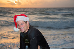 man in a wetsuit wearing a santa hat at the beach