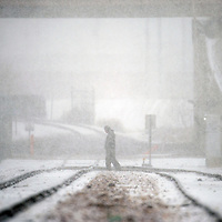 120413       Adron Gardner<br /> <br /> Snow blankets a man crossing the rail tracks parallel to North Ninth Street in Gallup Wednesday.