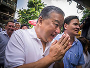 "16 JANUARY 2013 - BANGKOK, THAILAND:   SUKHUMBHAND PARIBATRA, candidate for Governor of Bangkok, ""wais"" (the ""wai"" is a traditional Thai greeting) voters as he arrives at a campaign function on Silom Road in Bangkok. The Oxford educated Sukhumbhand is a member of the Thai royal family (he is a great grandson of the late Thai King Chulalongkorn). He is a member of the Thai Democrat party and was first elected Governor of Bangkok in 2009. He is running for reelection this year. Sukhumbhand faces six challengers in the March 3 election. His toughest opponent is expected to be Police General Pongsapat Pongcharoen, who is running under the banner of the Pheu Thai Party, which controls the Prime Minister's office and Parliament.   PHOTO BY JACK KURTZ"