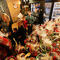 Children from Tupelo Children's Mansion enter KOK for dinner Monday night as they walk past 60 gift baskets that were provided for them by Farmhouse.