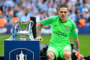 Ederson Moraes (31) of Manchester City sits next to the FA Cup on the podium during the celebrations at full time during the The FA Cup Final match between Manchester City and Watford at Wembley Stadium, London, England on 18 May 2019.