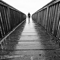 A lone man at the end of an old wooden pier in the rain.