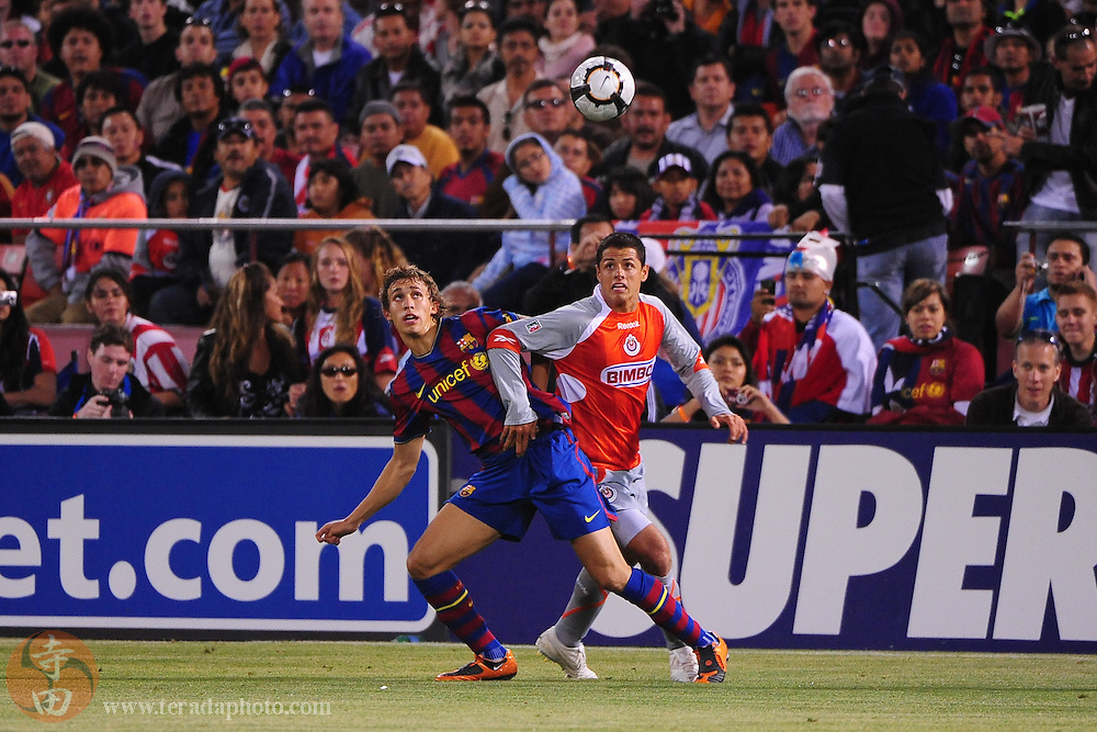 August 8, 2009; San Francisco, CA, USA; FC Barcelona defender Marc Muniesa (21, left) and Chivas de Guadalajara forward Javier Hernandez (14, right) fight for the ball during the first half in the Night of Champions international friendly contest at Candlestick Park.