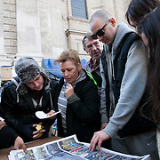 Campers looking through new paper coverage of the actions which have taken place all over the world. Day three of the occupation - and the first Monday. The Occupy London Stock Exchange movement was formed in London in solidarity with the US based Occupy Wall Street. The movements are a respons and in anger to what is seen by many as corporate greed and a failed banking system being bailed out by the public, - which in return are suffering austerity measures to make up for the billions of lost money. The movement occupied the St Paul's Square in the City of London Sat Oct 15 after it failed to secure and occupy Pator Noster Square and the Stock Exchnage itself.